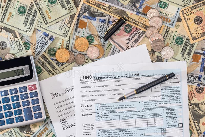 Us tax form and us money with calculator, coin. Closeup of us tax form and us money with calculator, coin royalty free stock photos