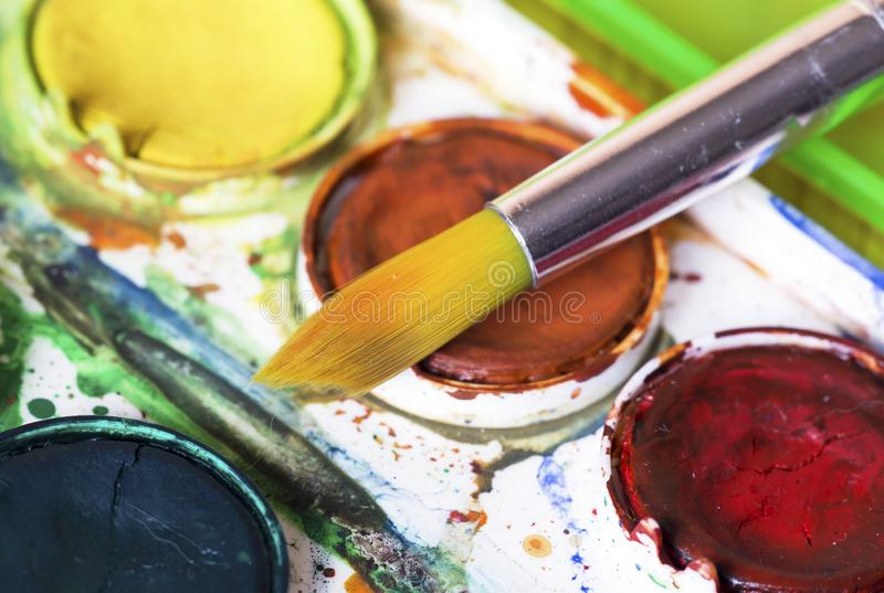 Closeup of used watercolor paintbox with brush stock image