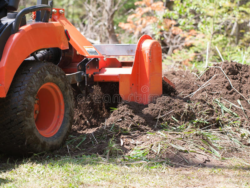 Closeup of a Utility Tractor With Tiller in Action stock photography