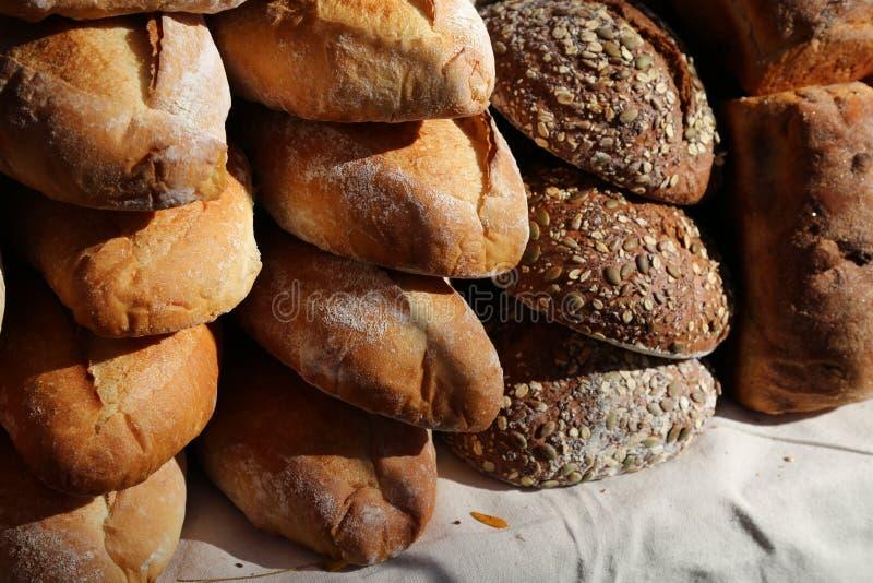 Closeup variety Artisanal bread loaves stacked on table- horizontal. Crusty artisanal loaves of bread stacked on a table. Crunchy crust fresh baked horizontal stock image