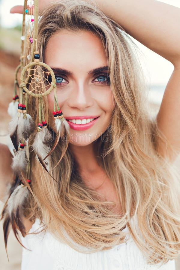 Closeup vertical portrait of pretty blonde girl with long hair on beach. She holds ornamentation with feathers in hand. Closeup vertical portrait of pretty stock photo