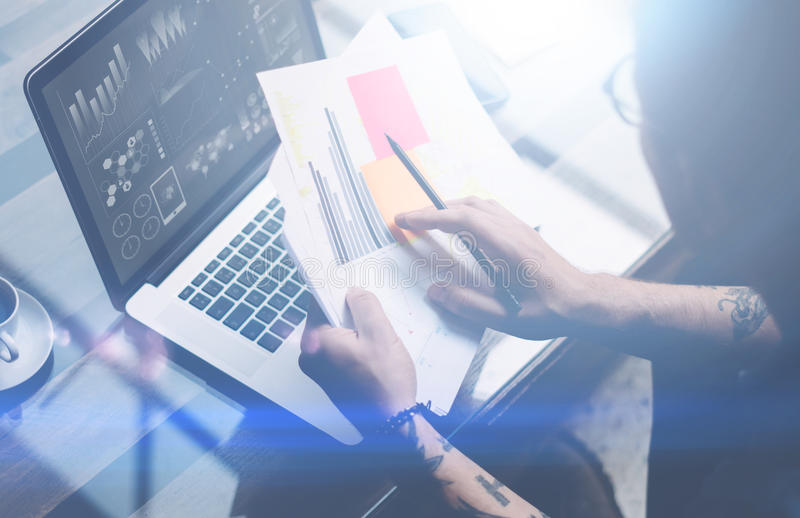 Closeup view of adult tattooed coworker working with laptop at workplace.Businessman analyze documents on hands.Graphs royalty free stock images