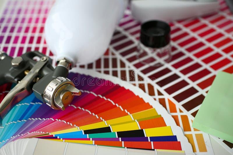 Closeup view of airbrush gun lying at colour check royalty free stock photo