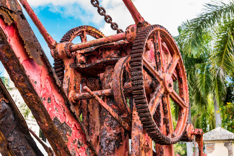 Closeup view of Antique red iron boat crane alone the shoreline stock photo
