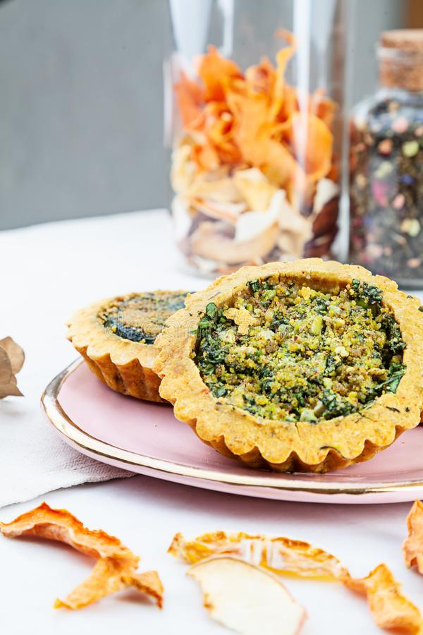 Closeup view on Baked homemade quiche pie on special mini forms. healthy vegan food. Pie served on pink plate on white marble royalty free stock image