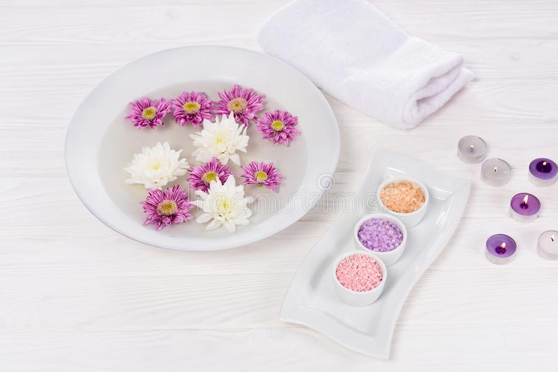 Closeup view of bath for nails with flowers at table with towel, colorful sea salt and aroma candles for manicure and pedicure В�. Closeup view of bath for royalty free stock images