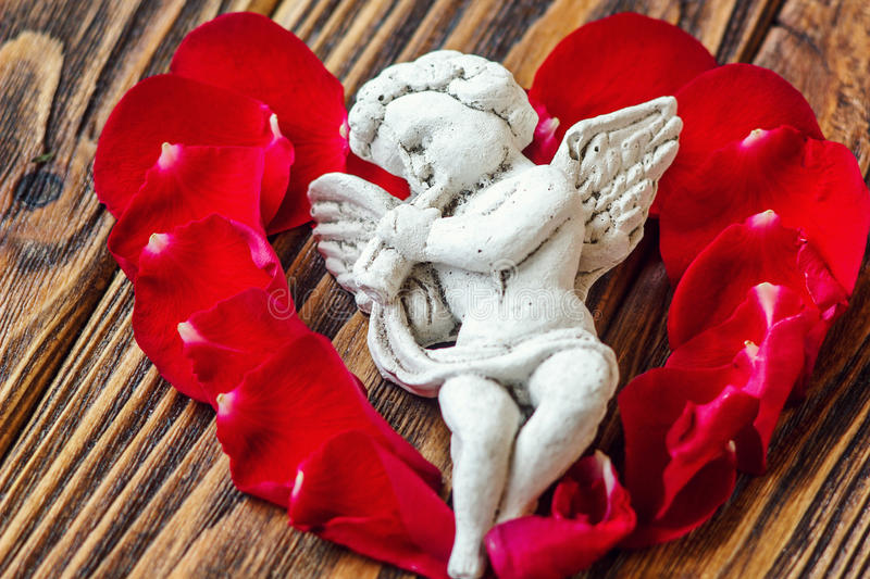 Closeup view of beautiful cupid with the trumpet, angel decorative figurine near red rose petals on wooden background. Greeting card . St Valentine's Day royalty free stock images