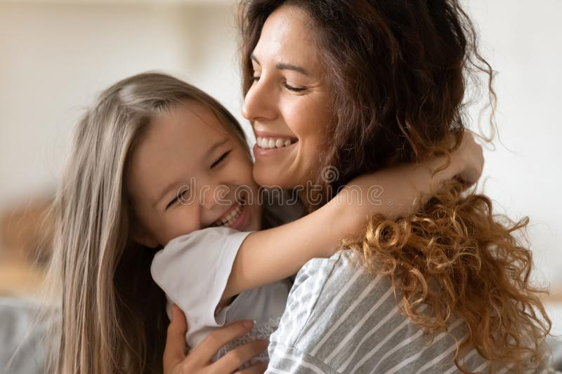 Closeup view beautiful young mother snuggle little cheerful daughter stock image