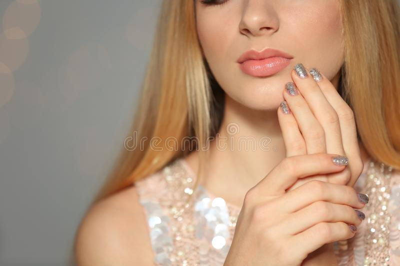Closeup view of beautiful young woman with shiny manicure on blurred background. Nail polish trends stock photo