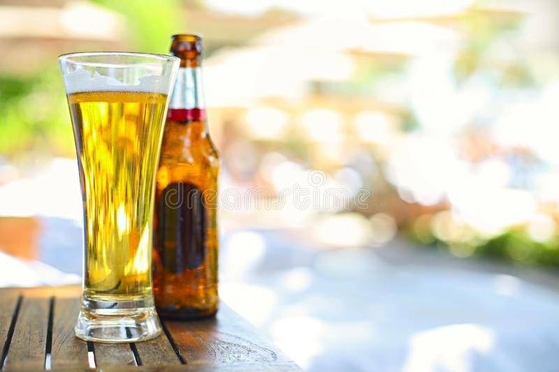 Closeup view of beer bottle and the glass in the garden royalty free stock image