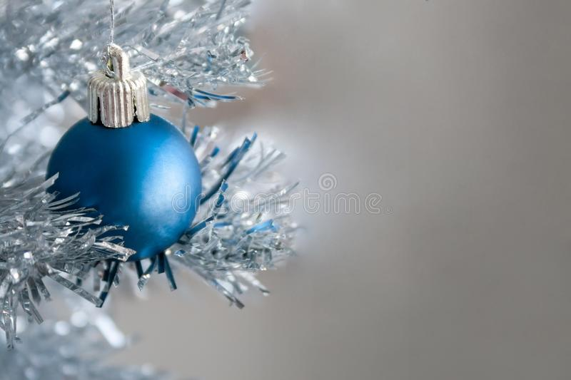 Closeup view of a blue matte ball hanging on a silver artificial Christmas tree with copy space for your text message stock images