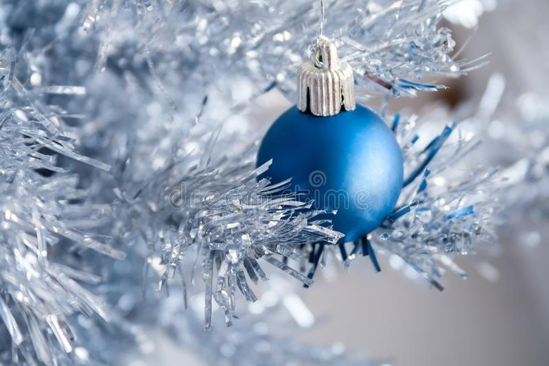 Closeup view of a blue matte ball hanging on a silver artificial Christmas tree. Selective focus. Blurred background royalty free stock photos