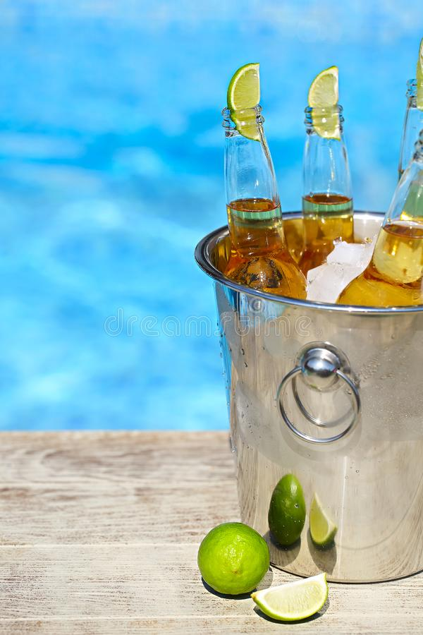 Closeup view of bucket with ice cubes, beer bottles and lime slices stock image
