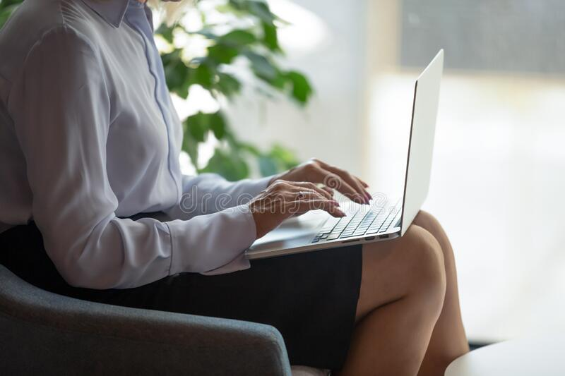 Closeup view businesswoman put computer on lap typing e-mail stock photography