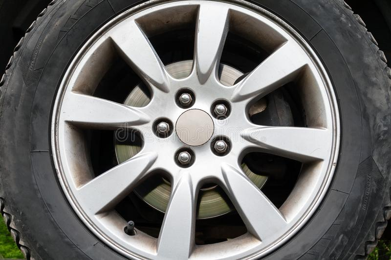 A closeup view of a car wheel with winter tires, silver brake disc and a five-nut rim stock photography
