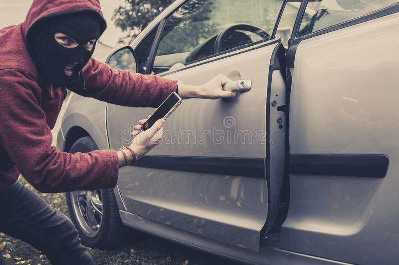 Closeup view of carjacker trying to open car with pick-lock. Masked man squats and breaks someone`s car looking to the stock image