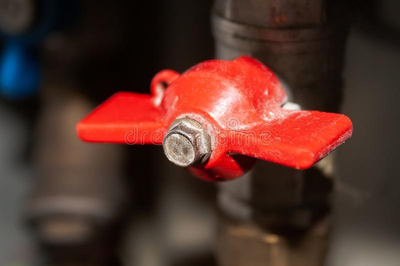 Closeup view on closed red valve on plastic and metal pipe with hot water. Hot water is turned off stock image