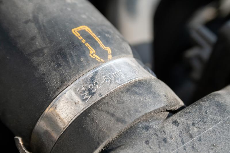 A closeup view of the dusty hose clamp on the car radiator hose, its markings and the yellow dotted arrow stock image