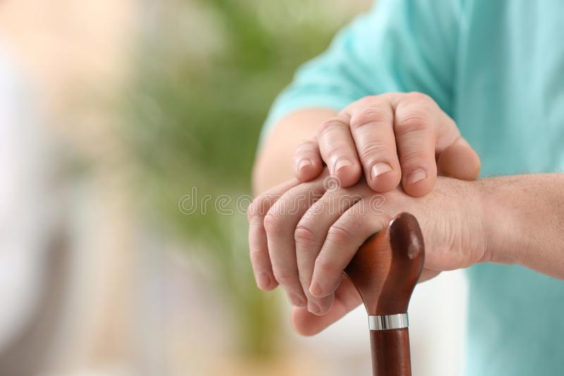 Closeup view of elderly man with cane in nursing home. Space for text. Assisting senior generation stock photography