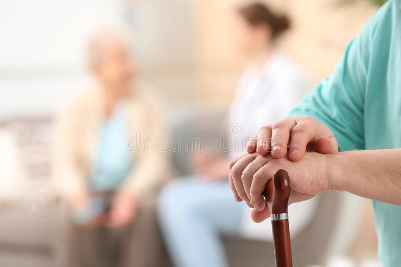 Closeup view of elderly man with cane in nursing home. Assisting senior generation stock photo