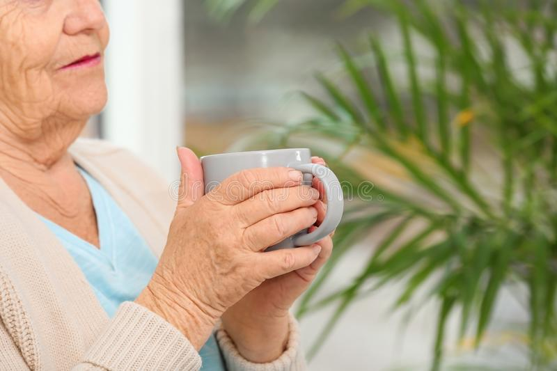 Closeup view of elderly woman with cup of tea in nursing home, space for text. Assisting. Senior generation stock photos