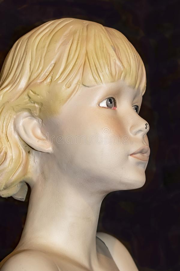 Closeup view of face of old retro mannequin girl with short blond hair and a chip in her nose and a spider behind her ear against royalty free stock photos