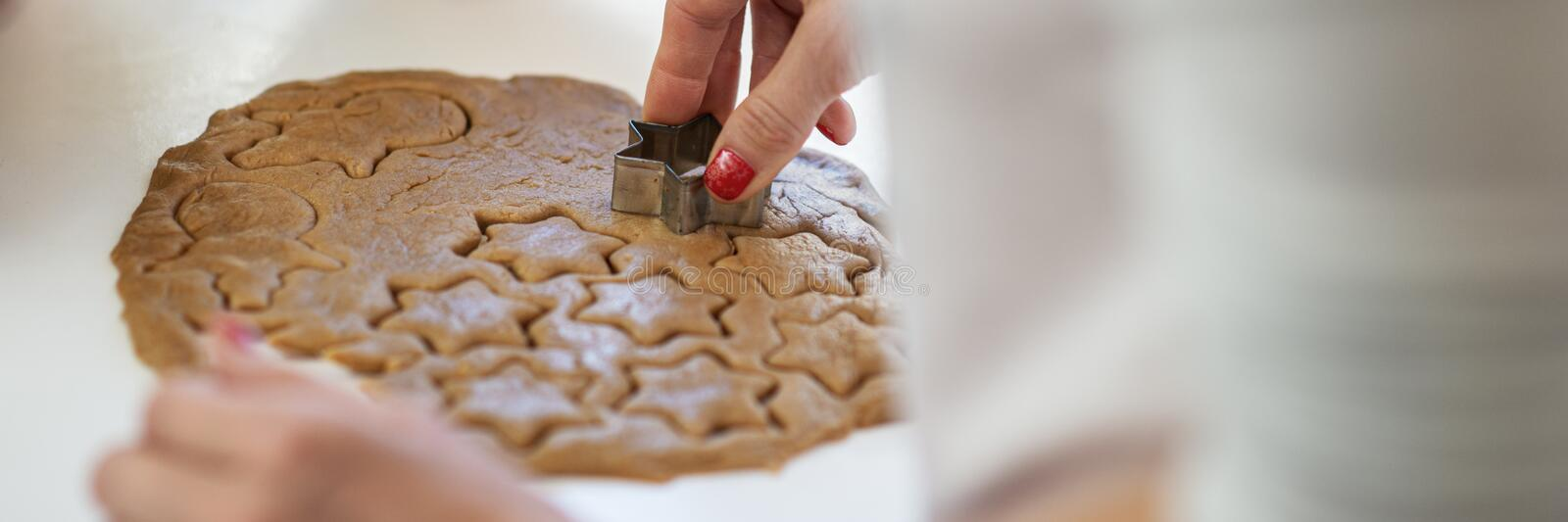 Closeup view of female hand making holiday cookies royalty free stock image