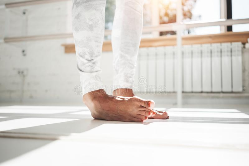 Closeup view on fit female legs stands on toes and doing stretching exercises wearing leggins indoor. Sunny gym royalty free stock photo