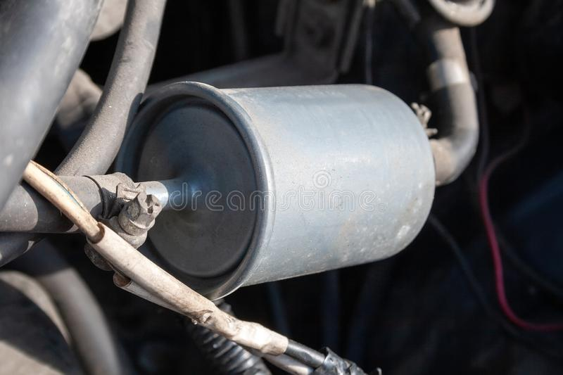A closeup view of a fuel filter installed in a car with a fuel line connected to it. Filter element in the fuel line. That traps particles of dirt and rust from stock photos