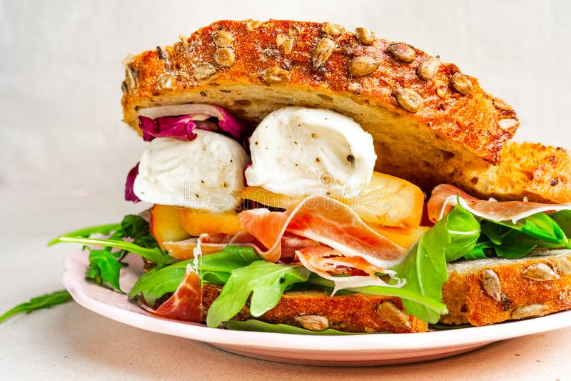 Closeup view of a gourmet Parma ham, mozzarella and peaches sandwich on a plate royalty free stock image