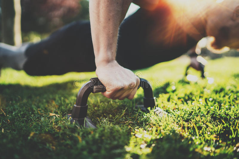 Closeup view of Handsome sport man doing pushups in the park on the sunny morning.Healthy lifestyle concept.Training. Outdoors.Blurred background.Visual effect royalty free stock images