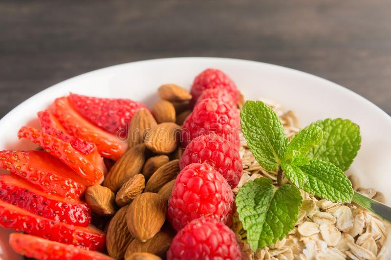 Closeup view of healthy breakfast bowl with oatmeal, strawberries, raspberries and almonds stock photo
