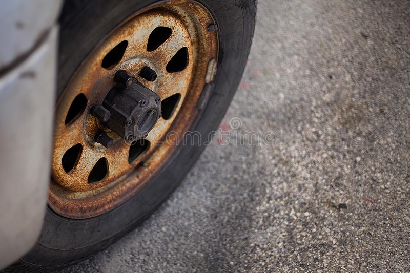 A closeup view of a heavily used car tyre that seems abandoned for a long time. There are also rusted rim, hubcap and screws that. A closeup view of a heavily royalty free stock image
