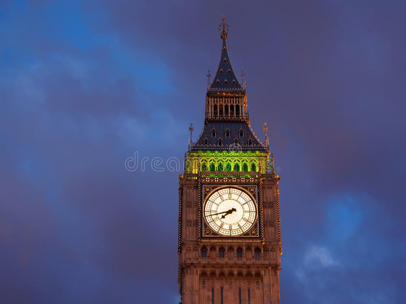 Closeup view of the illuminated Big Ben clock of the Elizabeth tower in London at dusk. royalty free stock photography