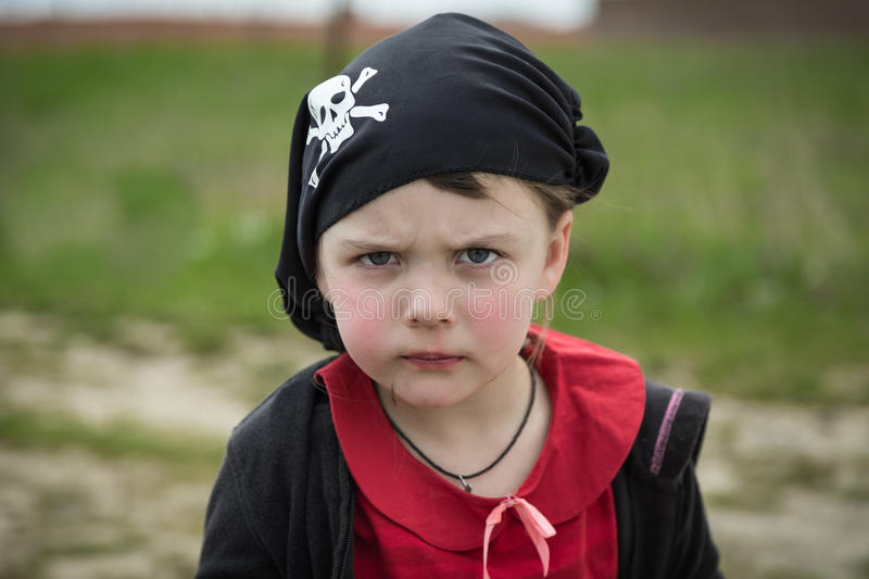 Closeup view of little serious pirate girl portrait wearing black banadana stock image