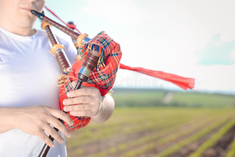 Closeup view of man enjoying playing pipes in traditional style. Green outdoors summer field background stock photos