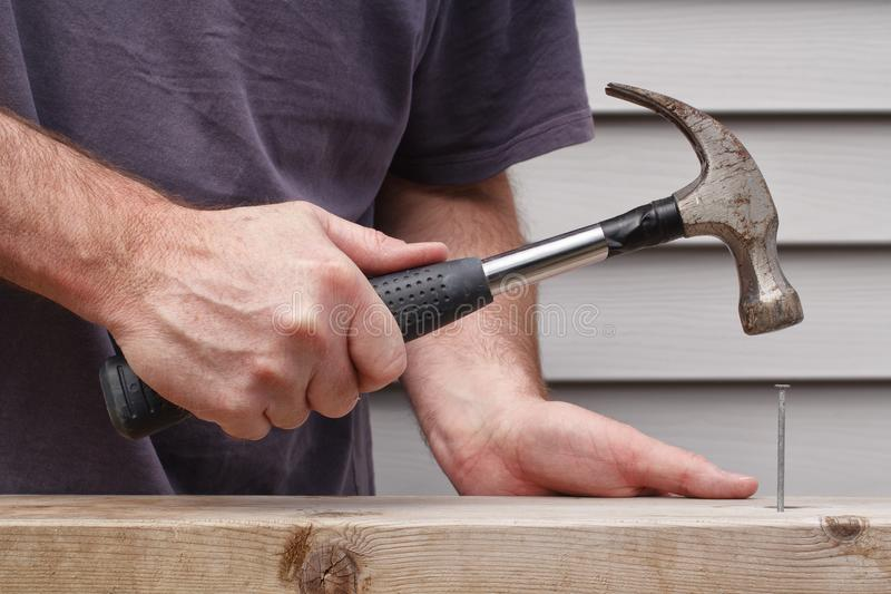 Man Hammering Nail. Closeup view of man hammering nail with house siding in background royalty free stock images