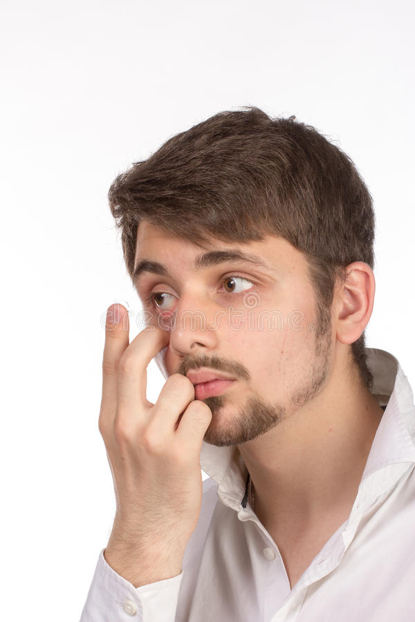 Closeup view of a man's brown eye while inserting a corrective c royalty free stock photos