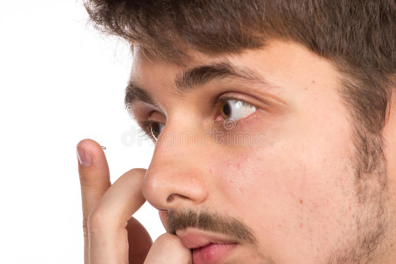 Closeup view of a man's brown eye while inserting a corrective c royalty free stock images