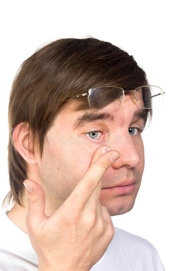 Closeup view of a man's brown eye while inserting a corrective c. Ontact lens on a finger stock images