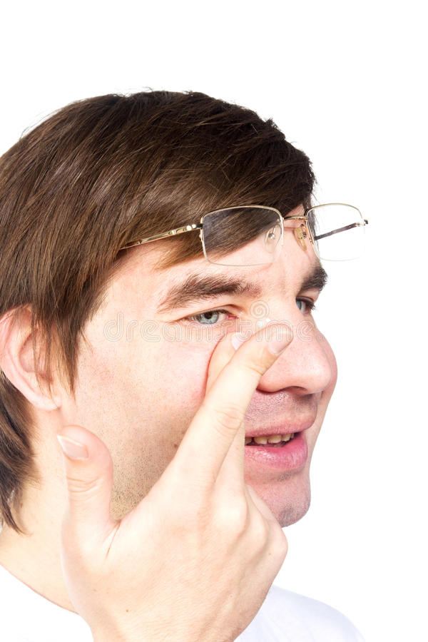 Closeup view of a man's brown eye while inserting a corrective c. Ontact lens on a finger stock photo