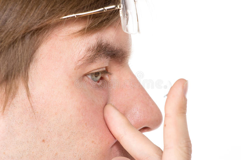 Closeup view of a man's brown eye while inserting a corrective c. Ontact lens on a finger stock image
