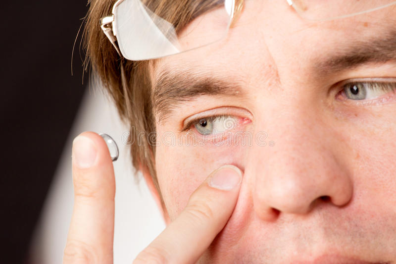 Closeup view of a man's brown eye while inserting a corrective c. Ontact lens on a finger royalty free stock photos