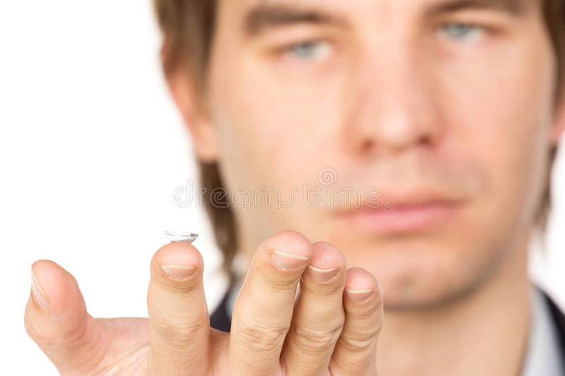 Closeup view of a man's brown eye while inserting a corrective c. Ontact lens on a finger royalty free stock images