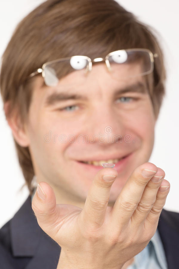 Closeup view of a man's brown eye while inserting a corrective c. Ontact lens on a finger stock photos