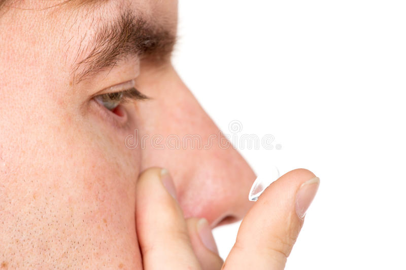 Closeup view of a man's brown eye while inserting a corrective c stock photos