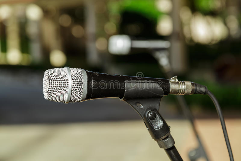 Closeup view of microphone detailed head against blurred outdoor background royalty free stock images