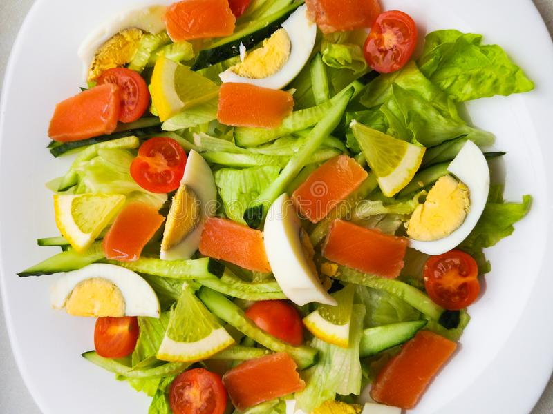 Closeup view of plate full of fresh green salad with mint leaves, yellow corn, tomato, tuna fish served with juicy lemon sauce. stock image