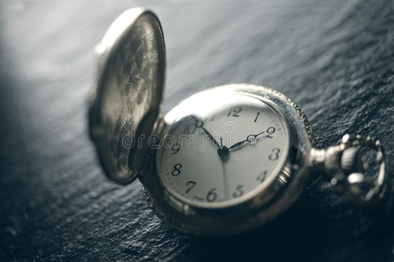 Closeup view of a pocketwatch on a slate - soft focus technique, stock photos