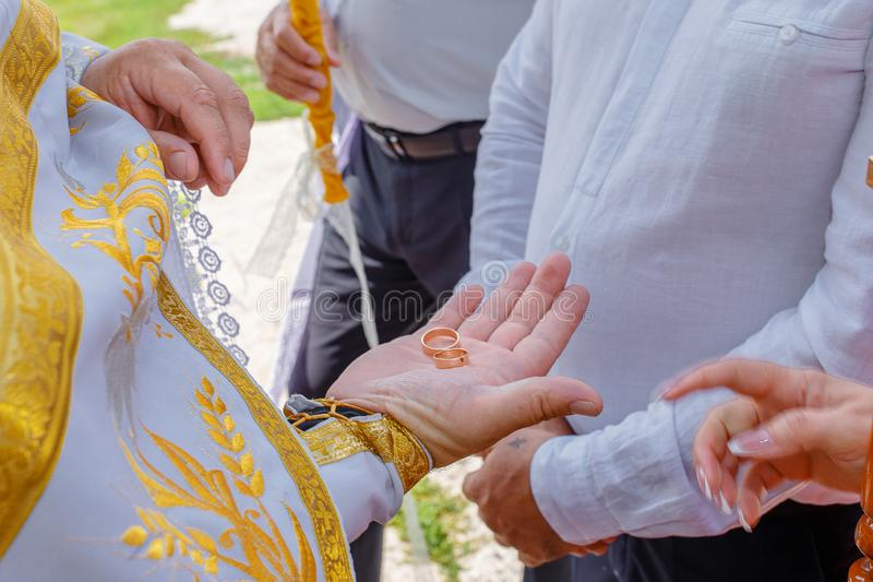Priest holds wedding rings stock photos